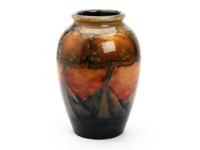 William Moorcroft 'Eventide' a vase,circa 1925 of ovoid form,with a continuous band of six trees 24.5cm high signed in blue and impressed, Moorcroft, Made in England. Rim cracked in three places, and repaired