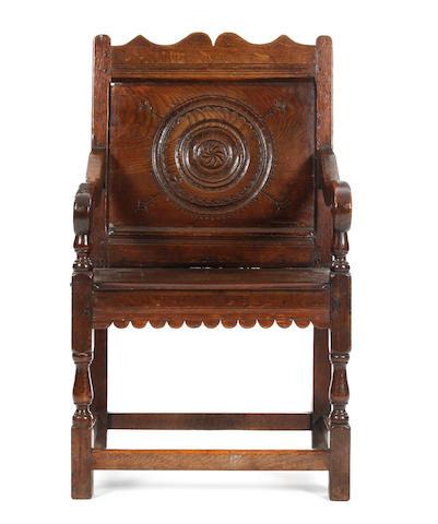 A late 17th Century oak panel back open armchair