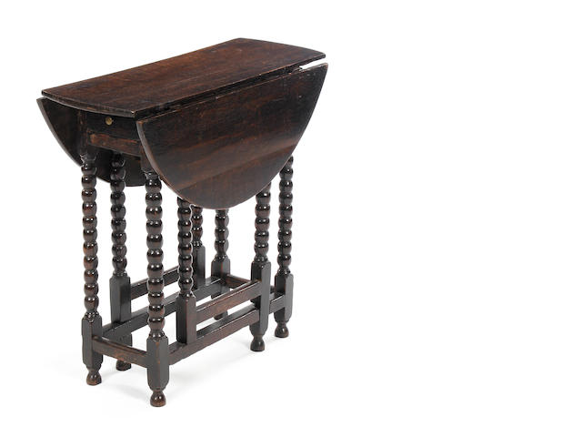 An oak gateleg table with bobbin legs.
