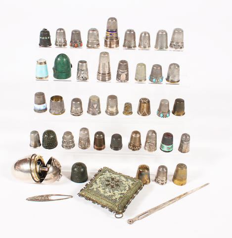 A silver egg shaped etui and a group of thimbles, most 19th century