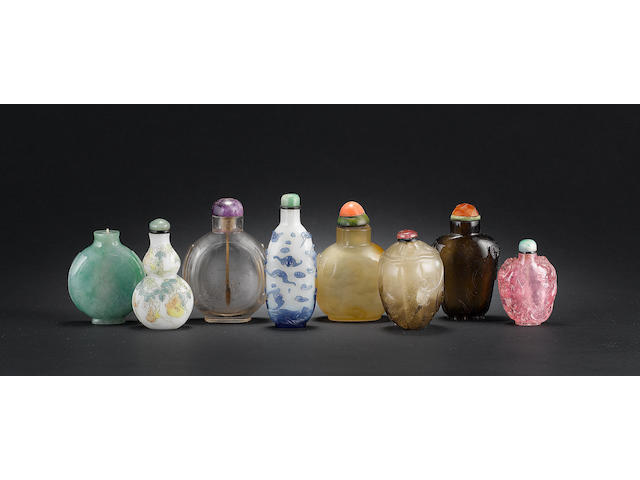 A mixed group of 8 snuff bottles, comprising: 3 crystal, 1 chalcedony, 1 jadeite, 1 blue overlay with bats, 1 rose quartz and 1 enamelled glass bottle of double gourd form (one missing stopper)