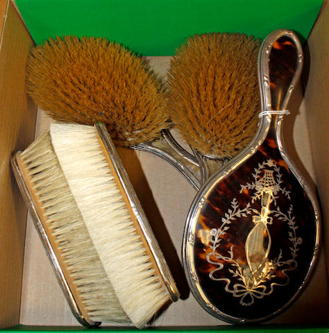 A tortoiseshell and silver pique five piece dressing table set,a pair each of hair abd clothes brushes and a hand mirror, inlaid with baskets of flowers, ribbons and swags, Birmingham 1907