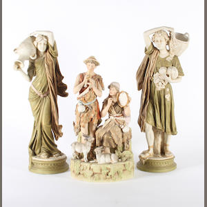 A pair of Royal Dux figures of water carriers and a Royal Dux figure group, circa 1900