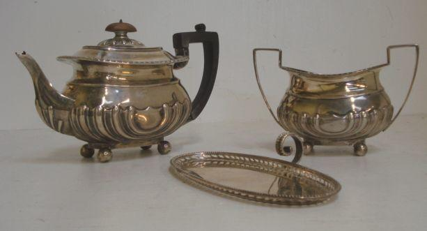 A late Victorian silver bachelor teapot and sugar basin, Hamilton & Inches, Edinburgh 1898, in Regency style, embossed curved lobes and flutes and a George III style silver snuffers tray, C & R.C., 1925, oval with pierced sides, bead edge and scroll handle, 24ozs. (3)