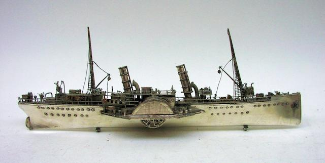 A white metal model of a 19th century paddle steamer 13ins. (33cm)long.