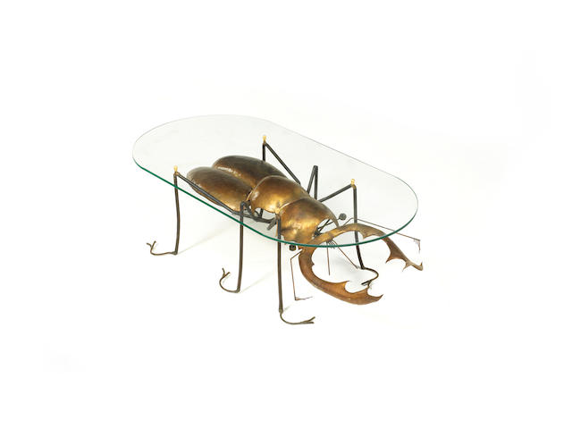 C 2345 François Melin A Coffee Table  circa 1970???  with glass top sitting on a metal base modelled as a stag beetle  Stamped Melin, Villoison, Villabé 30.5 by 100 by 49.5 cm. 12 by 39 3/8 by 19 1/2 in.