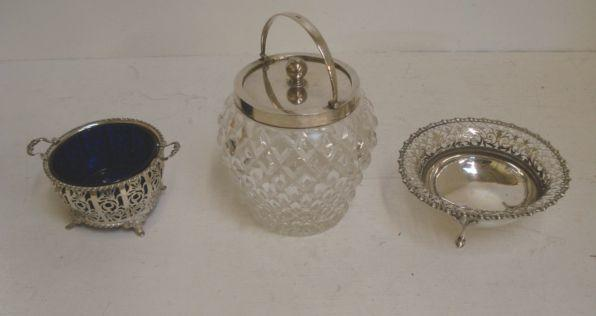 An Edwardian silver mounted cut glass biscuit barrel, Asprey, 1908, with hobnail cut sides, swing handle and pull-off cover, 20cm, and the following silver:- a pierced circular two handled basket, Adie Brothers, Birmingham 1932, with gadroon rims, on four splay feet, blue glass liner, 15cm across and an Edwardian circular bon bon dish, James Dixon & Sons, Sheffield 1906, with gadroon edge on three scroll feet, 15.5cm. (3)
