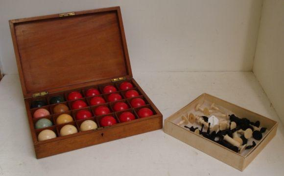 A collected carved and turned ivory chess set, one half stained black, Kings, 10cm, and a set of twenty four billiard balls, plain ivory or coloured, in a fitted rectangular mahogany case, the divided interior enclosed by a hinged cover,37 x 25.5cm.