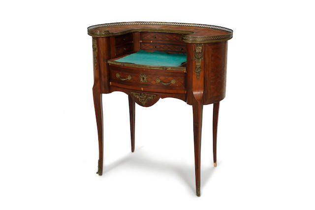 A parquetry kidney shaped writing desk