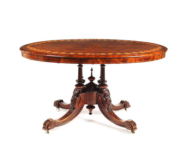 A mid Victorian inlaid walnut loo table, the oval well figured top with an inlaid border of leaves and berries on four cluster columns and carved downswept legs, 127 x 96cm.
