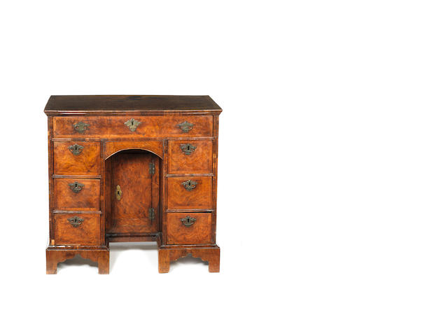 A Queen Anne walnut, crossbanded and featherbanded kneehole dressing table
