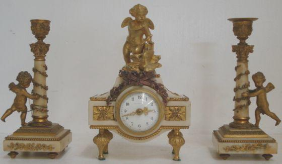 A 19th Century French white marble gilt metal mounted timepiece, the white enamel dial signed 'Thomas A Paris' and surmounted by a kneeling cherub and dove, 22cm, and a pair of matching candlesticks, with cherubs beside the classical columns, with key, 20cm.