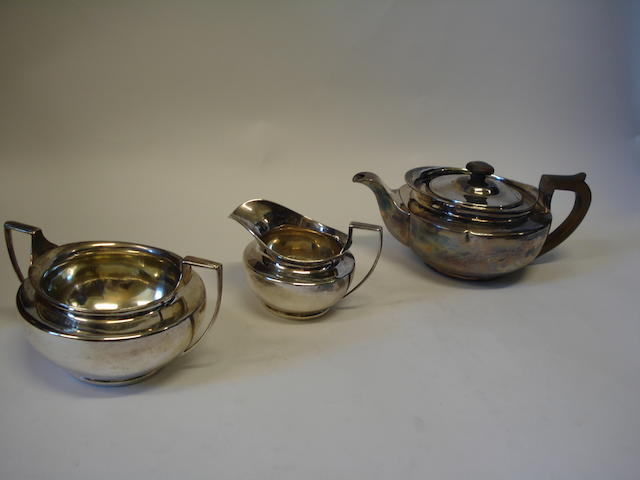 A matched George III/Victorian three piece silver tea service The teapot by William Burwash, London 1819, the sugar bowl and milk jug by Charles Stuart Harris, London 1884