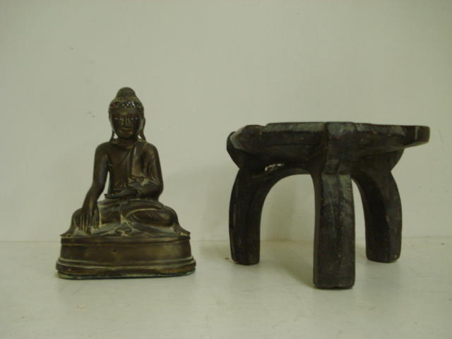 A small wooden stool, cultural origin, Hehe region, Tanzania, with dished circular top on three curved legs, 24cm, and a South East Asian gilt metal figure on a seated Buddha,22cm. (2)