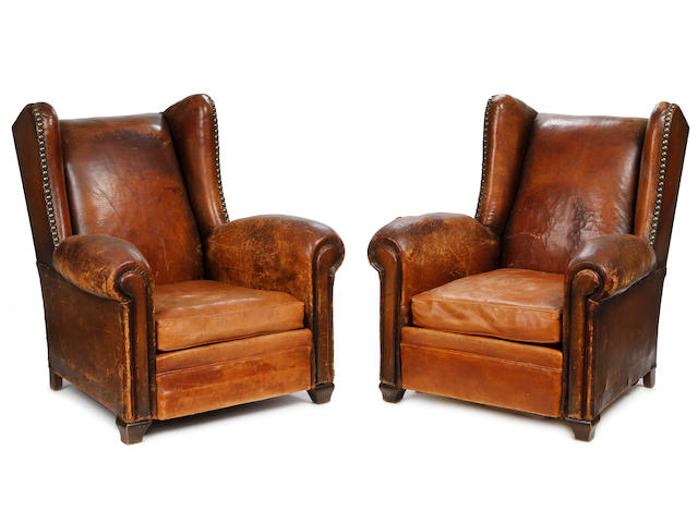 A pair of second quarter 20th century wingback club armchairs