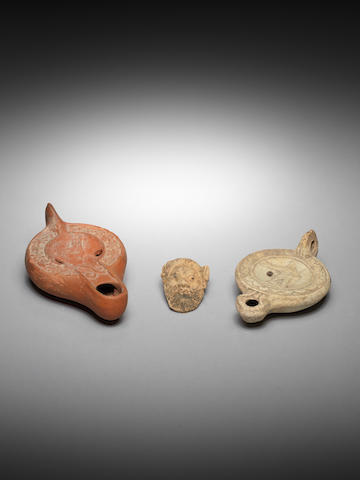 A Campanian terracotta appliqué mask and two Roman terracotta oil lamps, 3