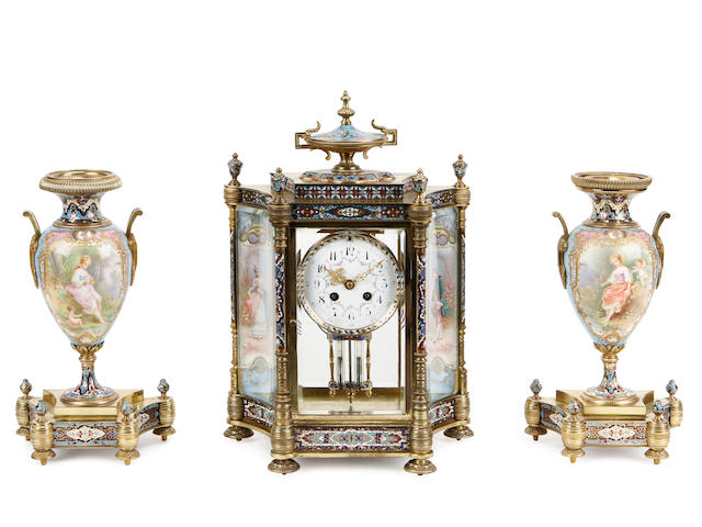 An early 20th century French porcelain mounted cloisonné enamel clock garniture
