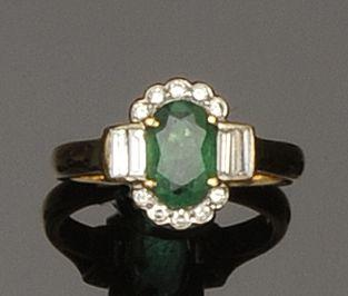 An emerald and diamond oval cluster ring