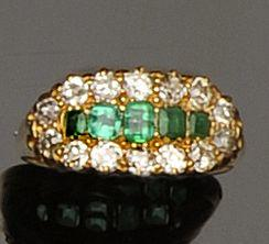 An emerald and diamond three row ring