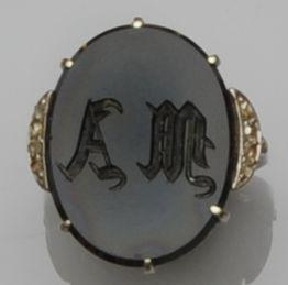 An oval onyx set memorial ring