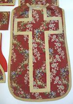 A brocade chasuble woven with trailing roses on a red ground