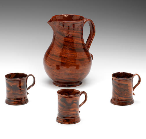 A large red and black agateware jug and three small red and black agateware mugs
