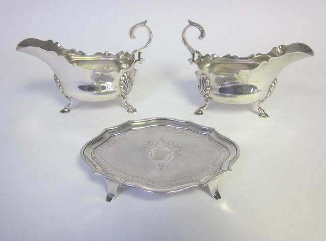 A pair of 18th century style silver sauceboats, by Martin Hall & Co, Sheffield 1909,  together with a George III silver shaped-oval teapot stand, by Stephen Adams, London 1795 (3)