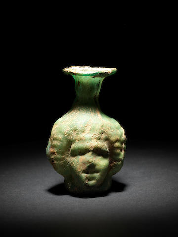A Roman streaked green glass janus head flask and a purple glass janus flask, 2