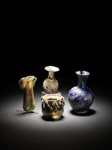 Three Roman green glass vessels and an Islamic blue glass flask, 4