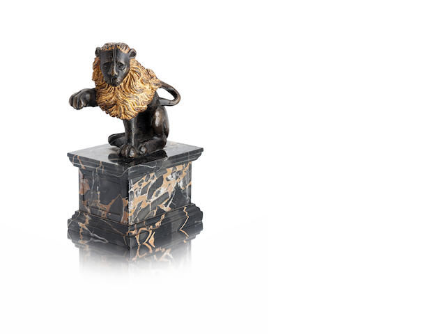 An Italian Renaissance style patinated and gilt bronze model of a seated lion