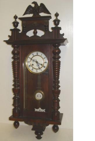 A 19th Century Vienna style walnut and ebonised case wall clock, with turned finials and fluted pilasters, the two part dial with Roman numerals, the 8 day movement striking on a gong, 125cm, and a similar smaller example in a walnut case with eagle surmount, 86cm. (2)
