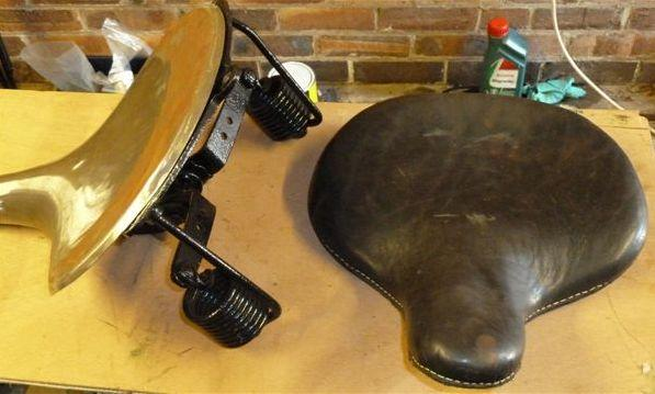 A pre-War motorcycle pan seat and leather cover,