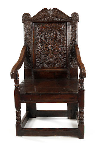 A Charles II oak panel back open armchair