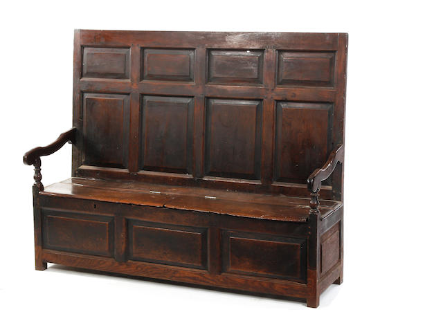 An 18th century oak high-back box settle