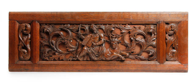 An early 18th century Flemish carved oak relief of St Luke