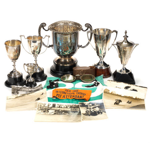 The Freddie Clarke Collection. To include six silver trophy cups, 75oz in all, 'No 29' cotton racing tabard, goggles, pit armband, laces, photos and cuttings.,
