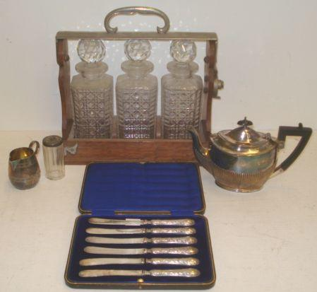 An Edwardian silver bachelor teapot, James Dixon & Sons, Sheffield 1906, in George III style, oval, part lobed and fluted, 9ozs, a cased set of six silver handled tea knives, an Edwardian electroplate mounted oak Betjemans patent Tantalus fitted with three cut glass decanters and other items.