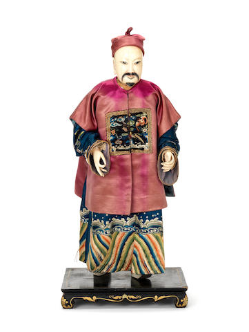 An exotic and rare early 19th Century ivory figure of a man with colourful and decorated silk clothes with natural hair added.