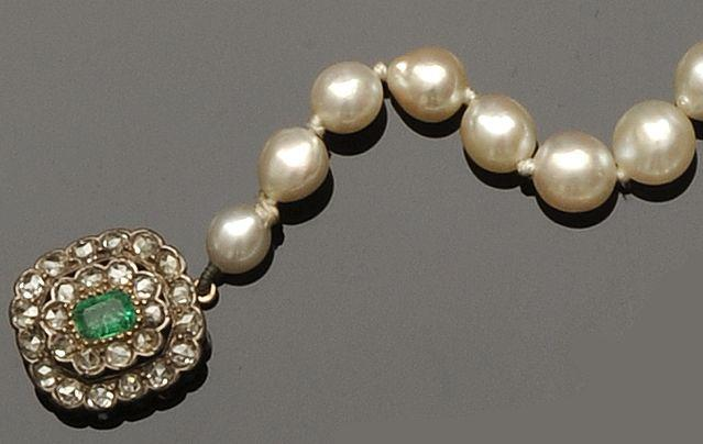 A cultured pearl necklace with emerald and diamond clasp