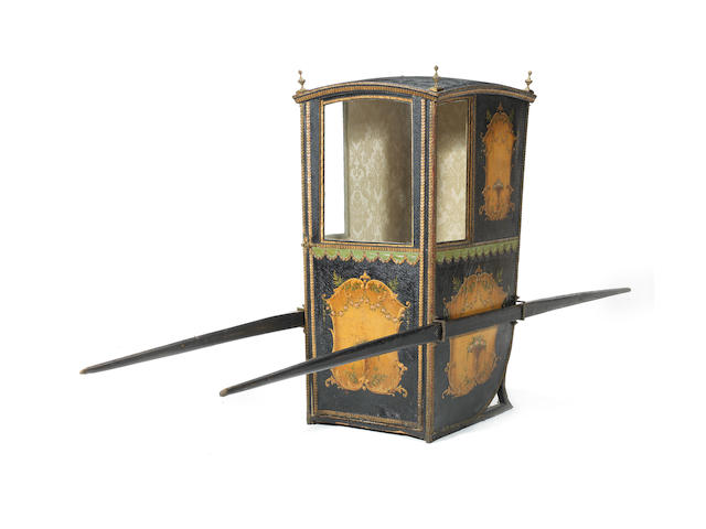 A late 18th century black and polychrome painted leather and giltwood carved sedan chair