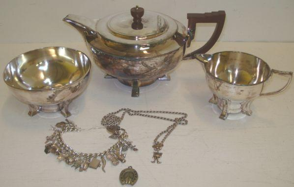 A stylish Art Deco electroplate three piece tea service, James Dixon & Sons, circular form on four feet, a silver curb link charm bracelet hung with a collection of charms, silver twisted link neckchain, hung with an articulated figure pendant and an electroplate horse shoe frame compass with ring attachment, 3ozs weighable.