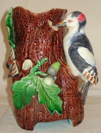 A Minton Majolica jug, modelled as a woodpecker on a tree trunk with acorns and leaves, ivy and a moth, impressed mark, registration kite mark and impressed numbers '1559', 18cm.