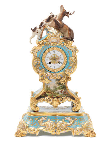 Painted porcelain and gilt mantel clock mounted with a dog and stag, with porcelain base, pendulum and key