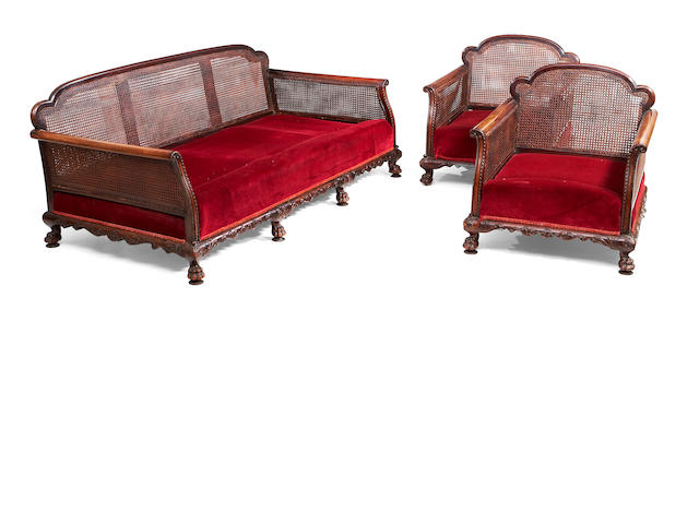 A three piece suite of early 20th century mahogany and double caned bergere furniture