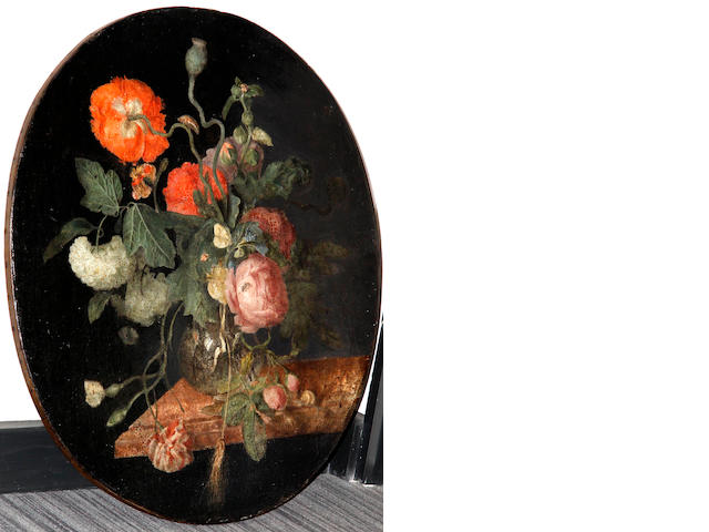 Manner of Jacob van Walscapelle A butterfly, poppies, roses and other flowers in a glass vase on a stone ledge