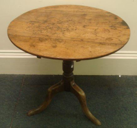 A George III oak tea table, restorations, the circular tilt-top on a turned pillar and tripod base, 81cm, and a waxed pine two tier cricket table, 65cm. (2)