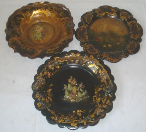 Two Victorian papier mache swing handle baskets, one inlaid with a family scene in mother of pearl within gilt borders, 26cm, the other painted with a face of flowers within rococo border, base stamped 'Jennins & Betridge' and a single plate. (3)