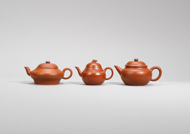 A small Yixing stoneware 'carp' teapot and cover, and two other teapots Qing dynasty, signed respectively Qiu Tong, Zhiyun Shi, Hui Pu