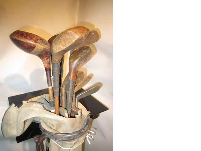 A collection of wooden shafted woods and irons in a distressed bag