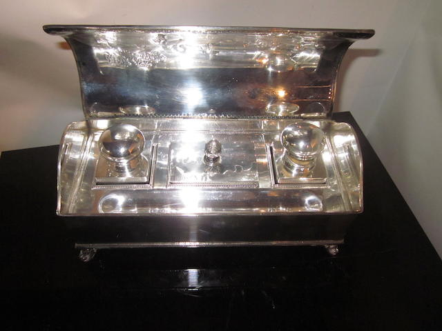 An Edwardian silver plated golf themed rectangular inkwell set on four scrolled feet